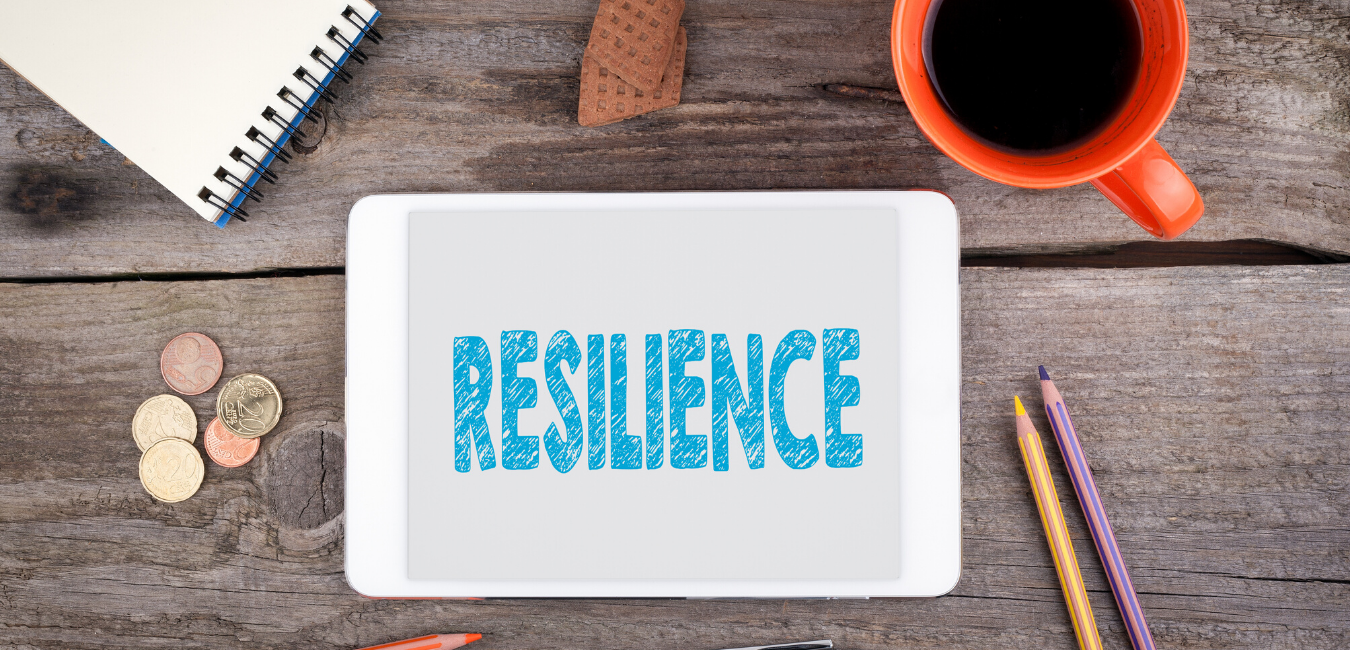 a photograph of a coffee bug, pencils, a notebook, and a tablet with the word resilience on it