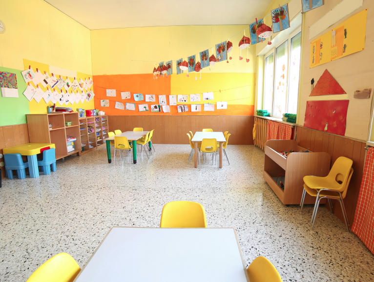 A photograph of an empty classroom, likely for very young children, with a table and three chairs in the foreground
