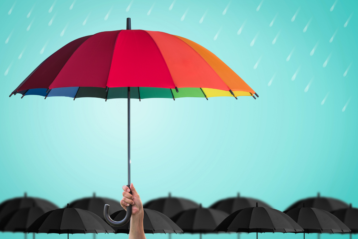 photo of a rainbow-coloured umbrella in front of several black umbrellas in the background