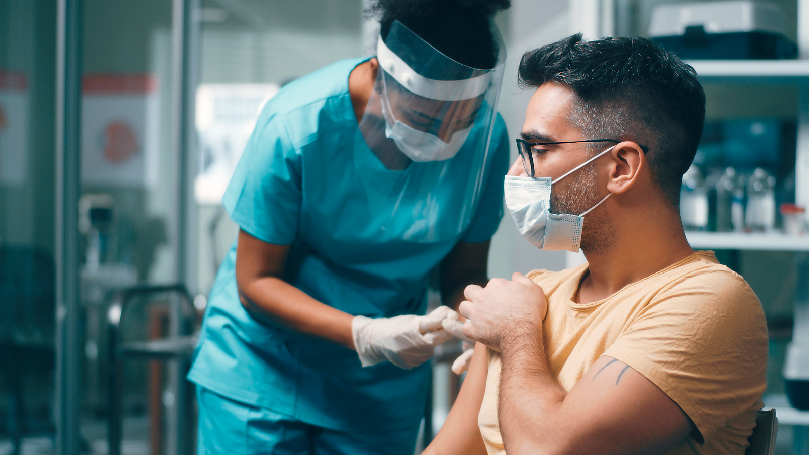 Photo of a woman in blue medical scrubs wearing a surgical mask and face shield injecting needle into the arm of a man wearing glasses and a surgical mask in a light orange t-shirt