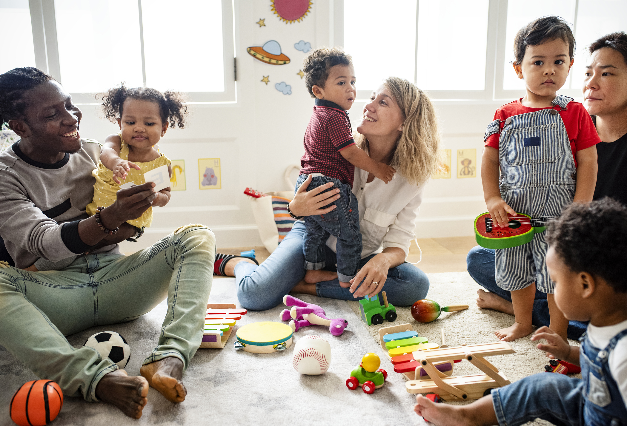 Children playing with toys alongside their parents