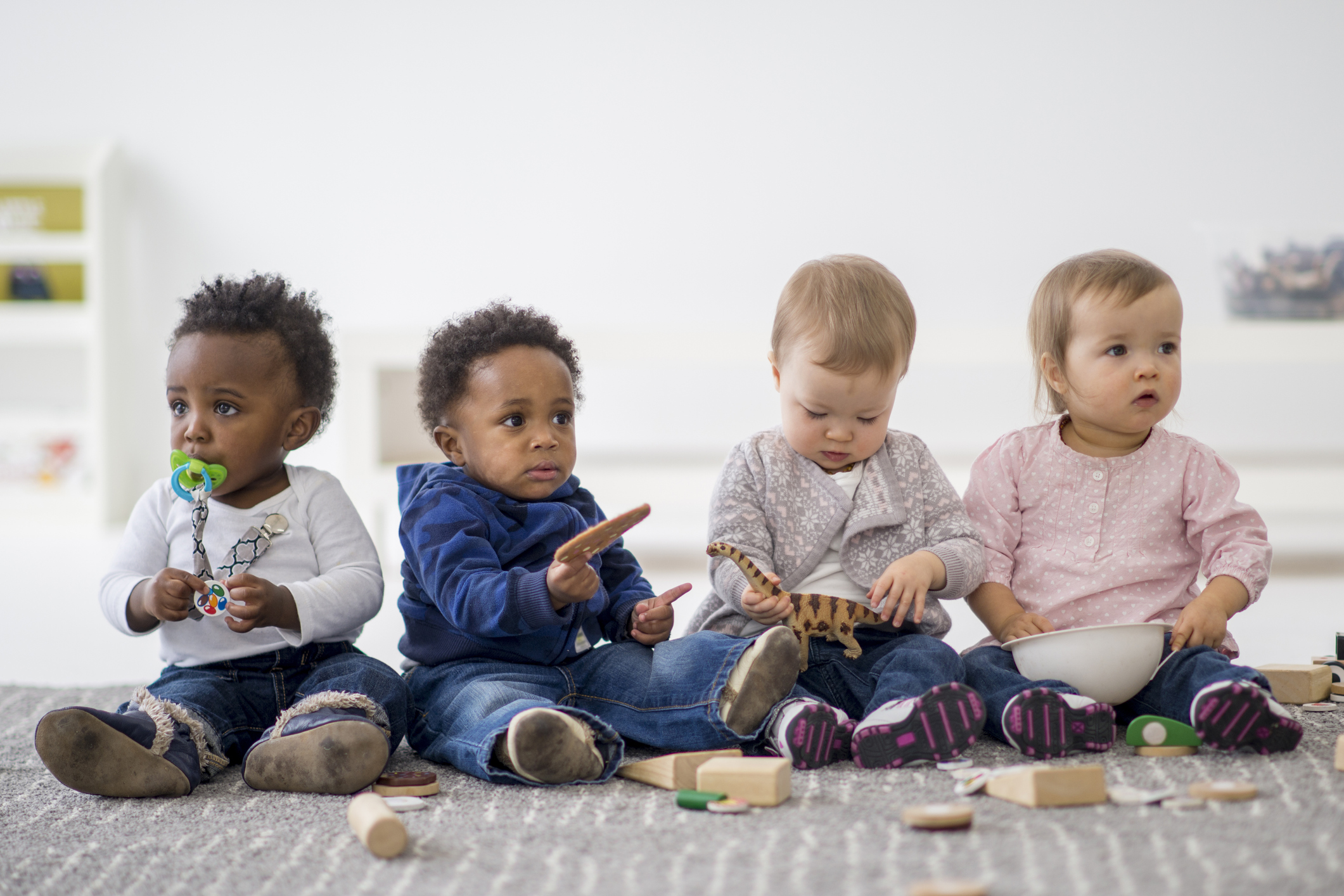 A multi-ethnic group of toddlers are sitting on the floor and are playing together with toys while on a play date.