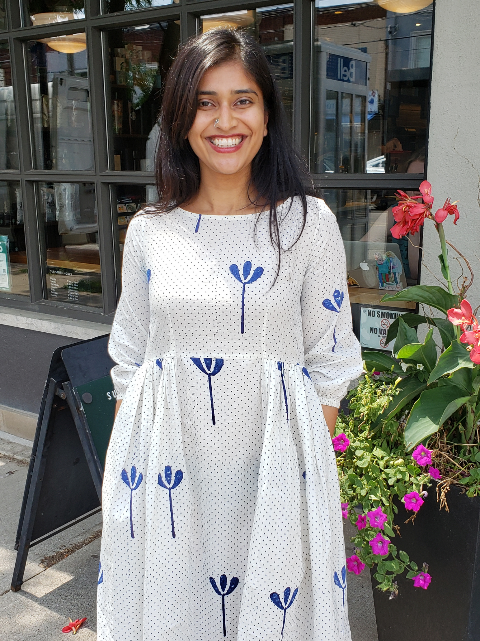 Kavita is on the sidewalk wearing a white dress posing outside a store/restaurant. Some red and purple flowers can be seen behind her. The glass windows of the store/restaurant reflect a bit of the opposite side of the street.