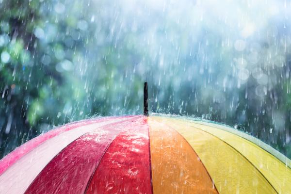 photo of a multicoloured umbrella in the rain