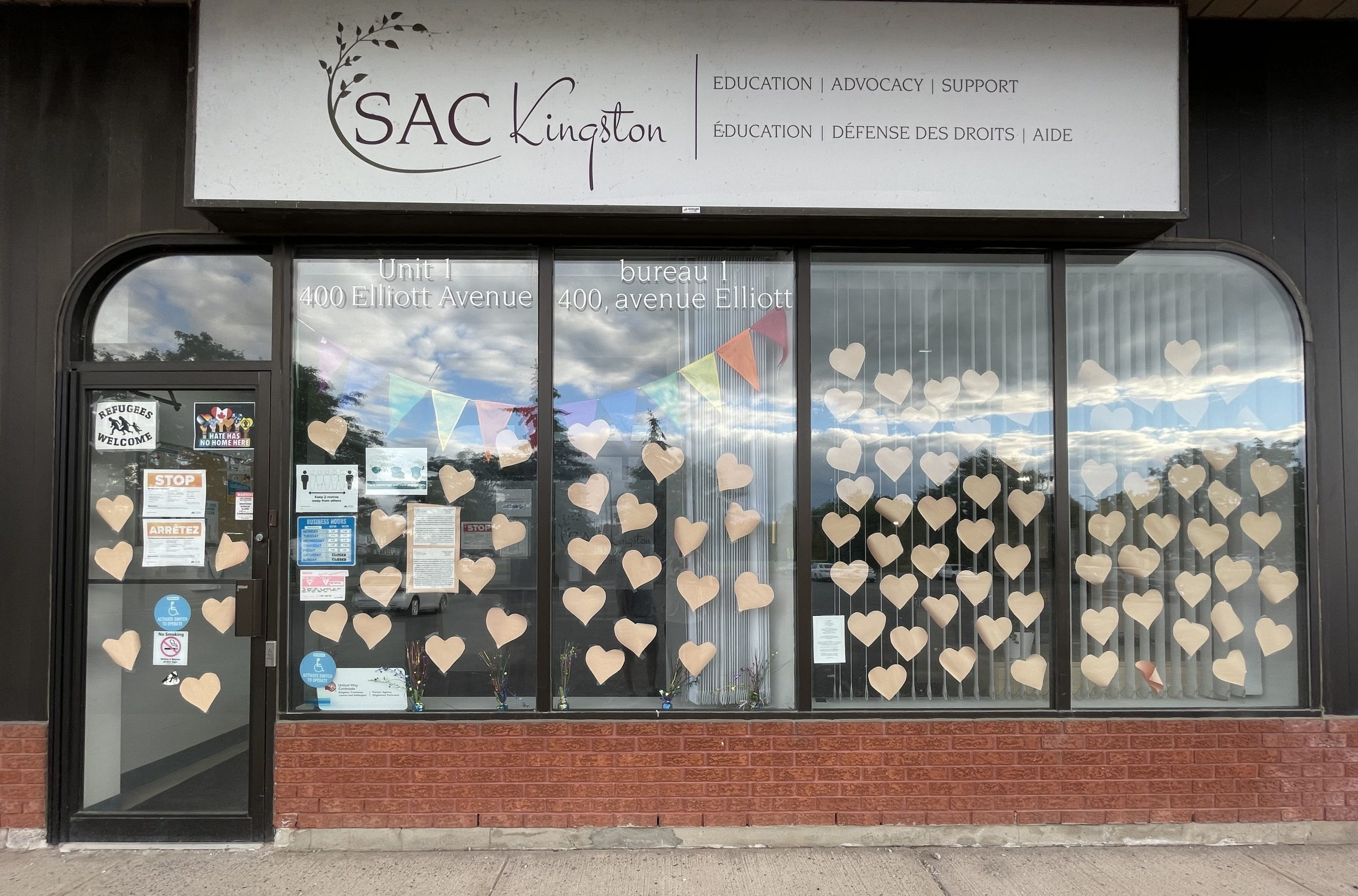 Image of SAC Kingston Office with their signage and windows covered with hearts.