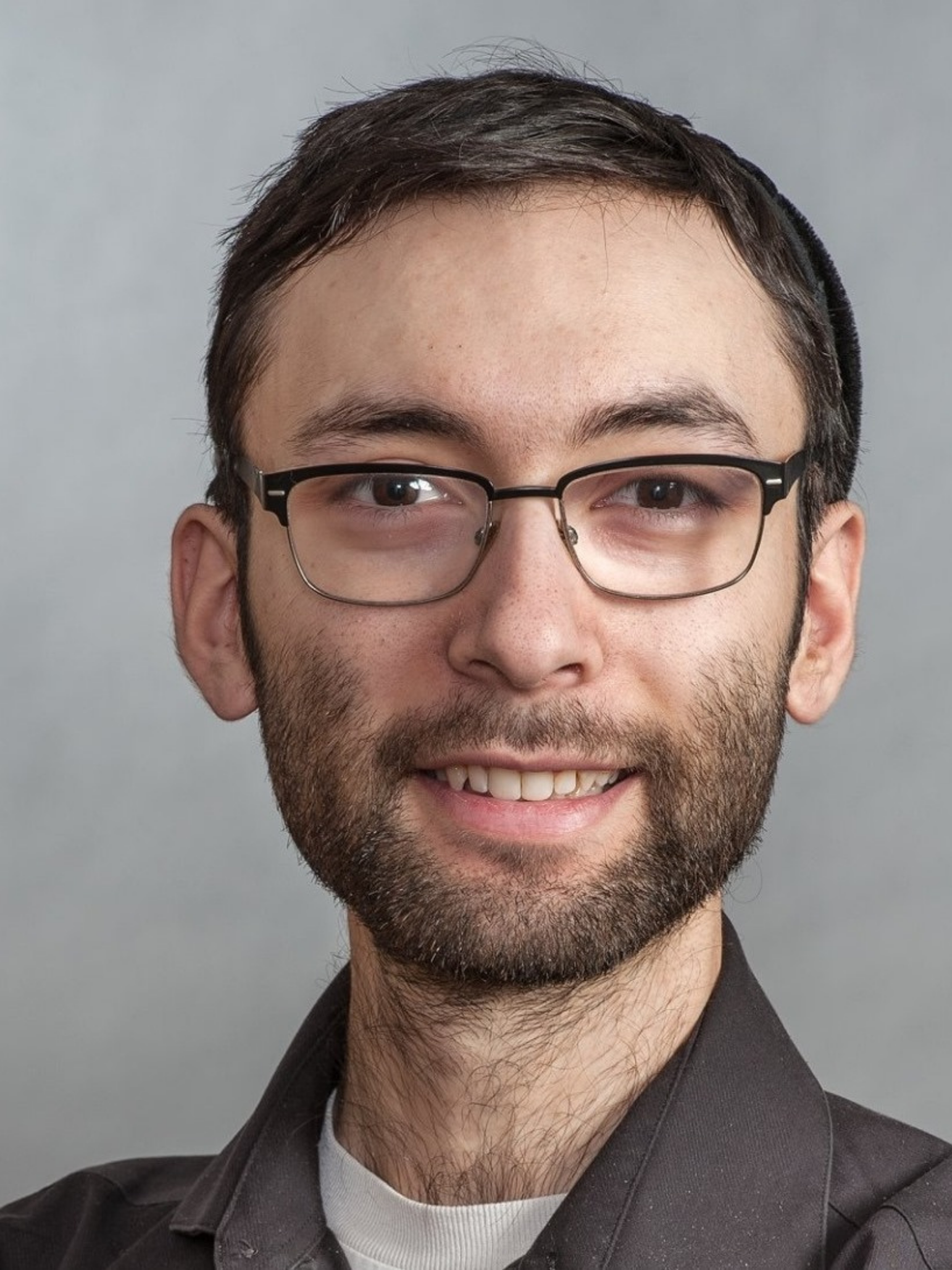 Benjamin Miller's headshot. Benjamin is facing the camera with a smile and wearing spectacles.