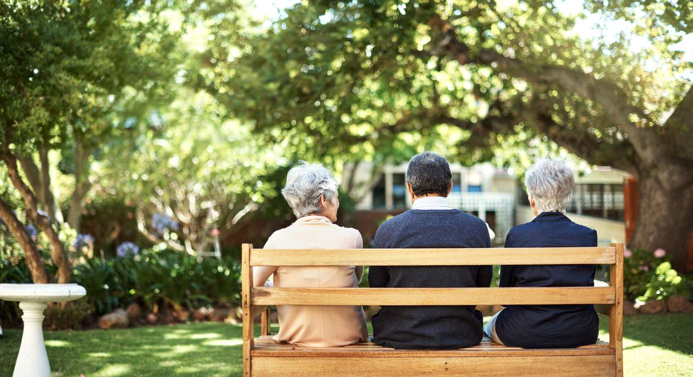 Rearview photograph of a group of seniors sitting together on a bench out in the garden